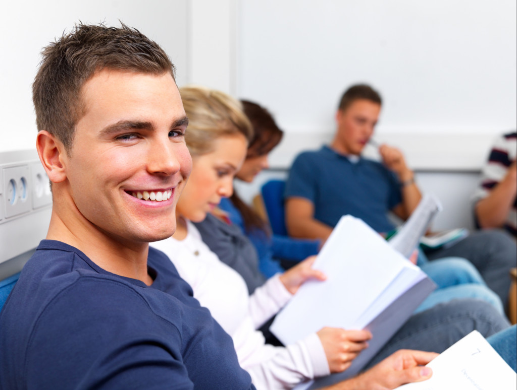 Happy young man sitting in class reading